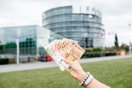 Het houden van Euro bankbiljetten op het Euoropean parlementsgebouw in Straatsburg, Frankrijk Stockfoto