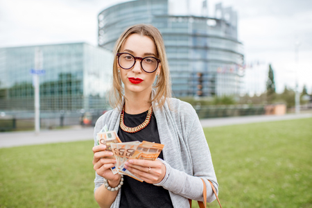 Portrait of a young and sad businesswoman counting money Stock Photo