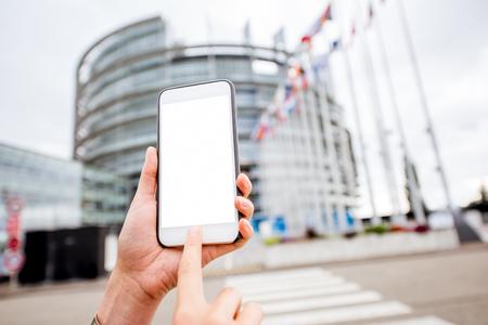 Het houden van een smartphone met het lege scherm om deeg op de Europese Parlementsgebouwachtergrond in Straatsburg, Frankrijk te kopiëren