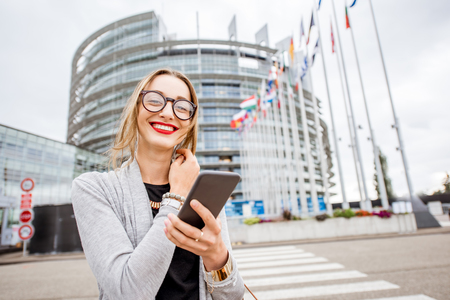 Levensstijlportret van een jonge vrouw die smartphone gebruiken die zich voor het Europese Parlementsgebouw in Straatsburg, Frankrijk bevinden Stockfoto - 90394229