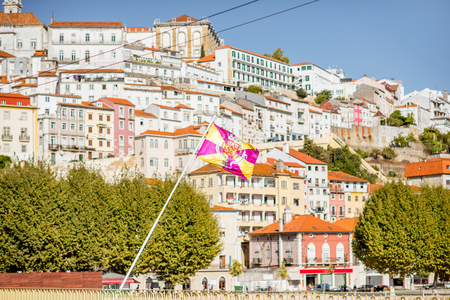Cityscape view on the old town of Coimbra city with flag in the central Portugal