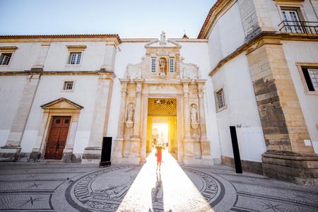Mening over de belangrijkste ingang aan de binnenplaats van het oude universitaire gebouw met vrouw die in de stad van Coimbra in centraal Portugal lopen