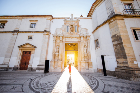 View on the main entrance to the courtyard of the old university building with woman walking in Coimbra city in the central Portugal