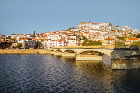 Cityscape view on the old town of Coimbra city with Mondego river and bridge during the sunset in the central Portugal