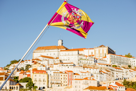 Cityscape view on the hill of the old town of Coimbra city with flag in the central Portugal