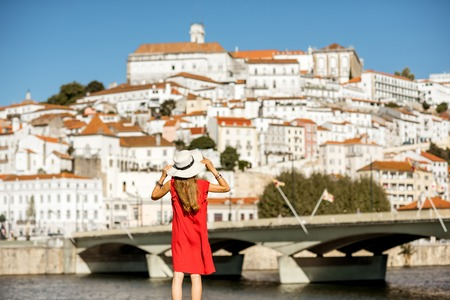 Young woman tourist in red dress enjoying great view on Coimbra city in the central Portugal Stock fotó