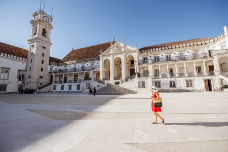 View on the courtyard of the old university building with woman walking in Coimbra city in the central Portugal