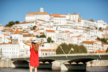 Young woman tourist in red dress enjoying great view on Coimbra city in the central Portugal Stock Photo