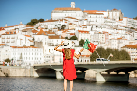 Young woman tourist in red dress enjoying great view on Coimbra city with portuguese flag in the central Portugal Stock Photo
