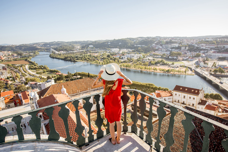 Young woman enjoying aerial view on the old town of Coimbra city during the sunset in the central Portugal Stock Photo - 89419845