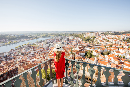 Young woman enjoying aerial view on the old town of Coimbra city during the sunset in the central Portugal Stock Photo - 90394590