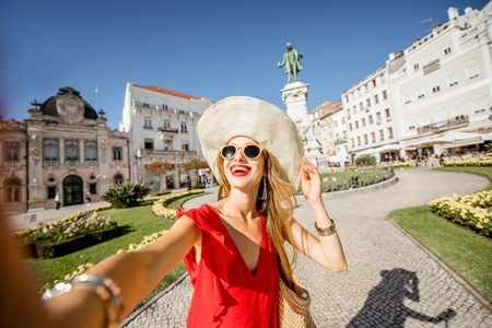 Young woman tourist making selfie photo standing on the central square in Coimbra city in central Portugal Stock Photo
