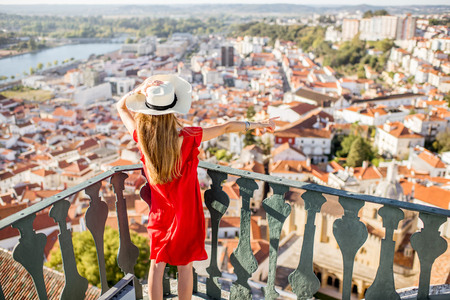 Young woman enjoying aerial view on the old town of Coimbra city during the sunset in the central Portugal