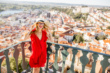 Portrait of a young woman standing on the aerial view background on the old town of Coimbra city during the sunset in the central Portugal