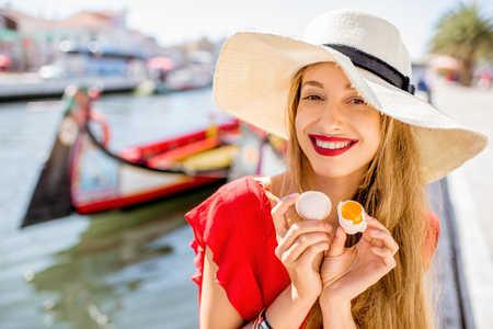 Young woman tourist holding portuguese delicacy called Ovos Moles made of egg yolks and sugar on the water channal background in Aveiro city, Portugal
