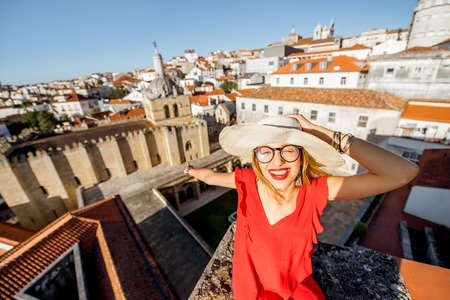 Portrait of a young woman tourist in red dress on the old city background traveling in Coimbra city in the central Portugal Stock Photo - 90394593