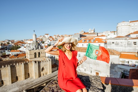 Portrait of a young woman tourist in red dress with portuguese flag on the old city background traveling in Coimbra city in the central Portugal