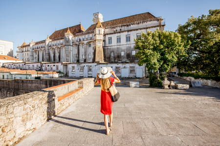 Woman in red dress walking back on the old university building background in Coimbra city in the central Portugal