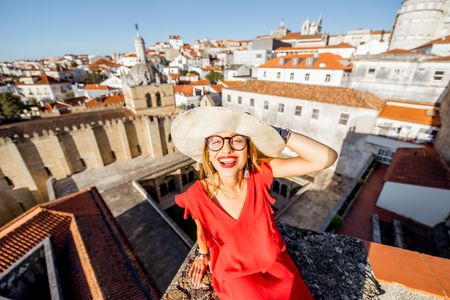 Portrait of a young woman tourist in red dress on the old city background traveling in Coimbra city in the central Portugal