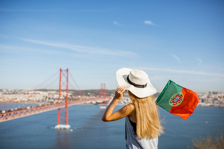 Young woman tourist enjoying beautiful aerial landscape view on the famous iron bridge sitting with portuguese flag in Lisbon city, Portugal