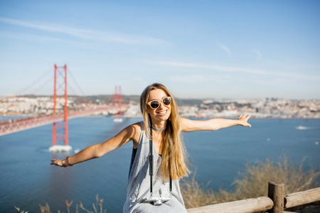 Woman having fun flying with hands on the beautiful landscape view background with iron bridge and river in Lisbon city, Portugal Reklamní fotografie - 89786732