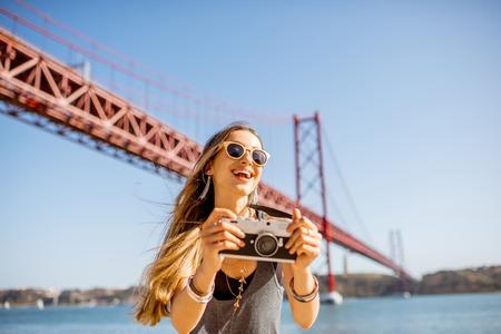 리스본 도시, 포르투갈 여행 유명한 철 다리 앞에서 사진 카메라 서와 젊은 여자 관광의 초상화 스톡 콘텐츠