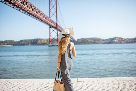 Lifestyle portrait of a woman walking on the riverside with beautiful iron bridge on the background in Lisbon city, Porugal Stock Photo