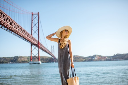 Lifestyle portrait of a woman walking on the riverside with beautiful iron bridge on the background in Lisbon city, Porugal Stock fotó