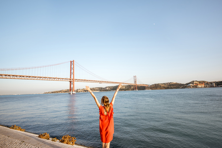 Woman in red dress enjoying landscape view on the famous iron bridge standing back on the riverside in Lisbon city, Portugal. Wide angle view with copy space Reklamní fotografie - 89786748