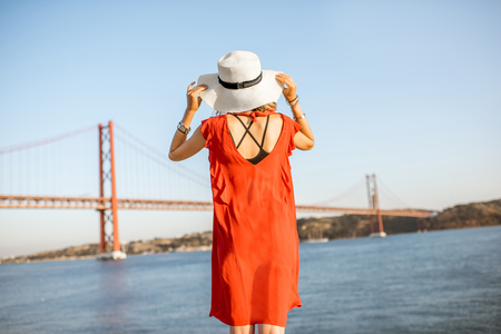 Woman in red dress enjoying landscape view on the famous iron bridge standing back on the riverside in Lisbon city, Portugal Reklamní fotografie - 89617235