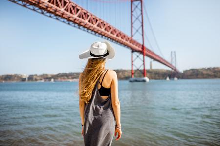 Woman enjoying beautiful landscape view on the famous iron bridge standing back near the river in Lisbon, Portugal Reklamní fotografie - 89617341