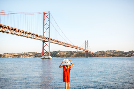 Woman in red dress enjoying landscape view on the famous iron bridge standing back on the riverside in Lisbon city, Portugal. Wide angle view with copy space Reklamní fotografie - 89787051