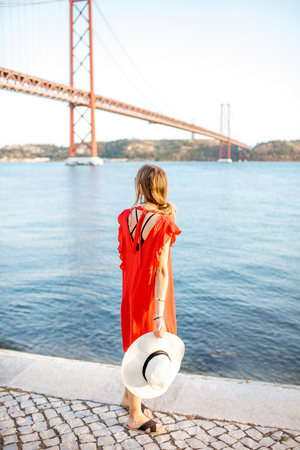 Woman in red dress enjoying landscape view on the famous iron bridge standing back on the riverside in Lisbon city.