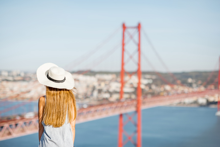 Young woman tourist enjoying beautiful aerial landscape view on the famous iron bridge in Lisbon city, Portugal Stock Photo
