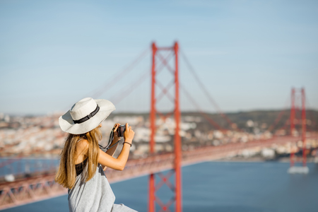 Portrait of a young woman tourist with photo camera sitting on the landscape view background with beautiful iron bridge in Lisbon city, Portugal