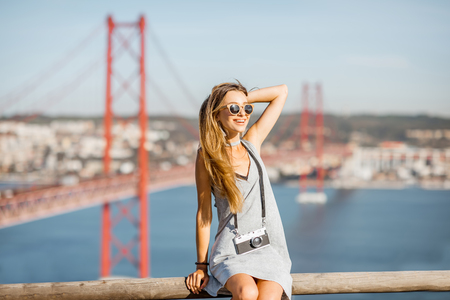 Portrait of a young and cute woman with photo camera on the landscape view background with beautiful iron bridge traveling in Lisbon city, Portugal