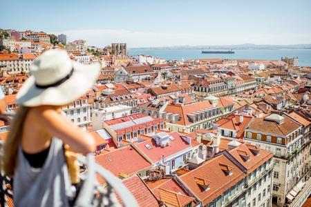 젊은 여자 관광 아름 다운 풍경을 즐기고 리스본 도시, 포르투갈에서 화창한 날 동안 오래 된 마을에서 상위 뷰. 배경에 중점을 둔 이미지