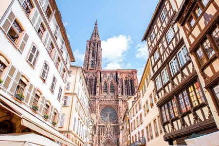 Street view from below on the beautiful old buildings and Notre-Dame cathedral in Strasbourg city, France