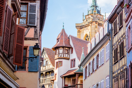 Street view on the beautiful old buildings with cathedral tower in the famous tourist town Colmar in Alsace region, France