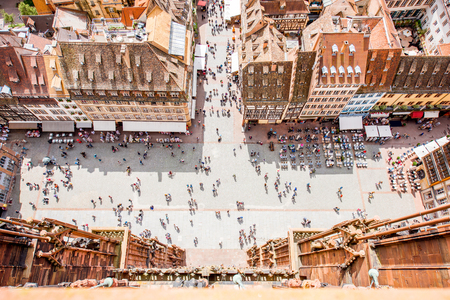 Top cityscape view on the cathedral square crowded with people in the old town of Strasbourg city, France