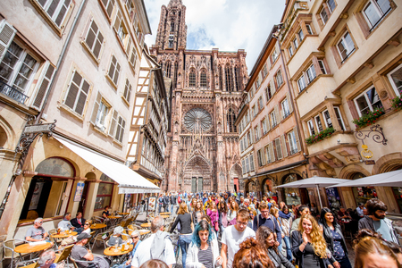 STRASBOURG, FRANCE - July 26, 2017: View on the crowded street with beautiful old buildings and Notre-Dame cathedral in Strasbourg city, France