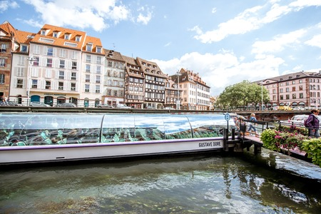 STRASBOURG, FRANCE - July 26, 2017: Landscape view on the water channel with tourist boat and beautiful half-timbered houses in Strasbourg city in Alsace region, France