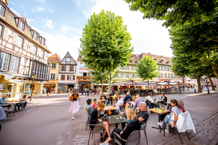 COLMAR, FRANCE - July 26, 2017: Street view with people sitting at the cafes and restaurants in the famous tourist town Colmar in Alsace region, France