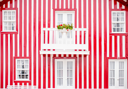 Facade view on the beautiful colorful striped house with windows and doors for background