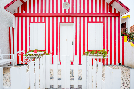 Facade view on the beautiful colorful striped house with windows and door for background Imagens
