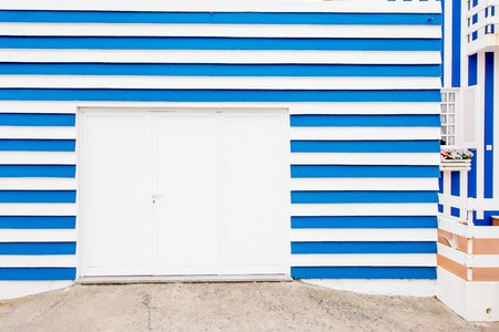 Facade view on the beautiful colorful striped house with garage doors for background
