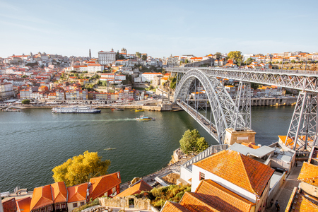 Landscape view the beautiful old town with famous iron bridge above the Douro river during the sunset in Porto city, Portugal Imagens