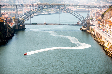 Landscpe view on the Douro river with speedboat floats and beautiful iron bridge in Porto city, Portugal