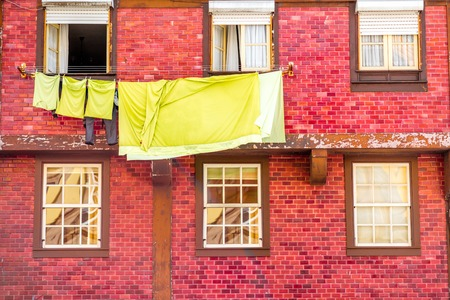 Cothes drying on the windows of the old red building in Porto city, Portugal Imagens
