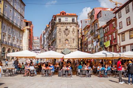 PORTO, PORTUGAL - September 25, 2017: View on the Ribeira square with tourists sitting at the bars and restaurants in Porto city, Portugal